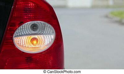 Flashing orange blinker light on rear lamp of car