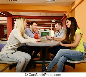 Group of four young smiling people chatting behind table in...