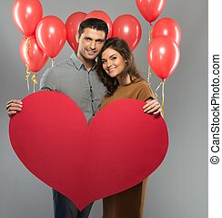 Happy couple handmade paper heart and red balloons