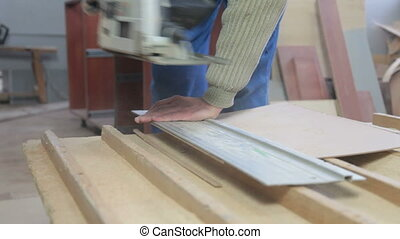 Carpenter cutting wood panel circular saw