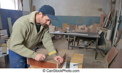Carpenter using hammer and nail woodworking