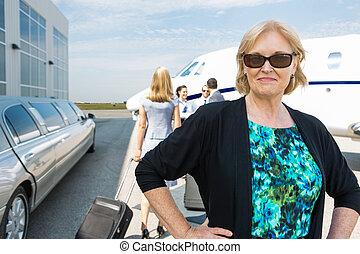Confident Businesswoman Against Private Jet - Portrait of...