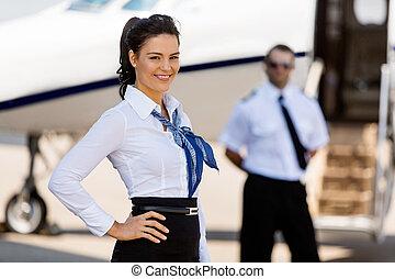 Airhostess, sonriente, con, piloto, y, privado, chorro, en,...