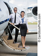 Full length portrait of confident airhostess and pilot...