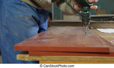Carpenter manufacturing furniture drilling a hole