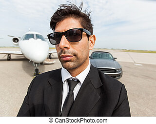Confident Businessman In Front Of Car And Private Jet -...