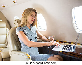 Confident Businesswoman Using Laptop In Private Jet -...