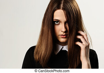 Portrait of a young beautiful woman touching her hair