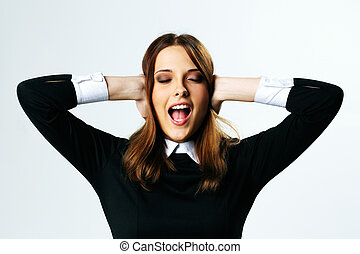 Portrait of a young woman closing her ears and screaming on...