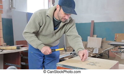 Carpenter assembling furniture in workshop