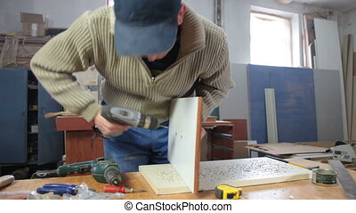 Joiner assembling furniture in workshop