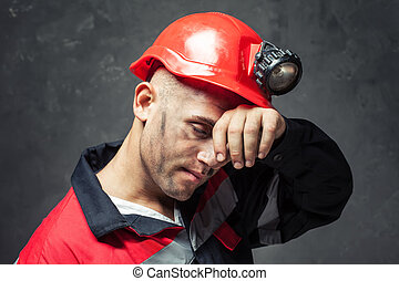 Portrait of tired coal miner wiping forehead his hand...
