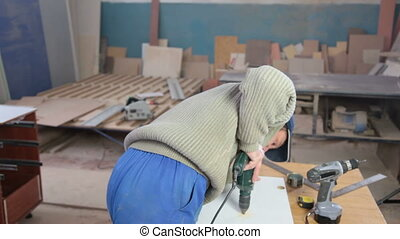 Carpenter using screwdriver assembling furniture