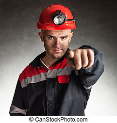 Coal miner pointing forward - Portrait of serious coal miner...