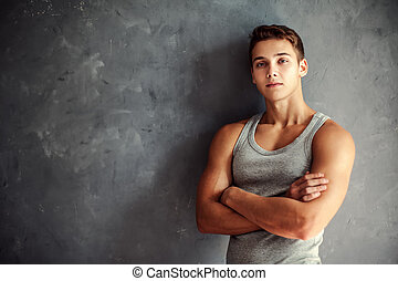 Portrait of muscular young handsome man wearing a gray...