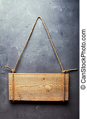 Wooden signboard hanging on rope on textured wall