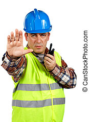 Construction worker with green safety vest worker talking...