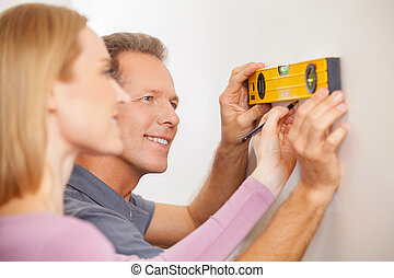Couple measuring wall. Cheerful mature couple taking measurements of the wall and smiling
