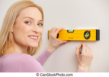 Handy around the home. Rear view of cheerful blond hair woman taking measurements of the wall and looking over shoulder