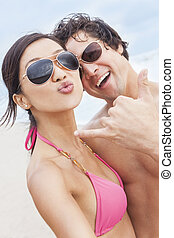 Asian Couple at Beach Taking Selfie Photograph - Man woman...