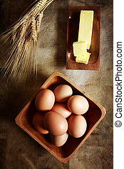 Eggs with butter and wheat on rustic wooden table