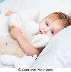 baby with a toys in white bed