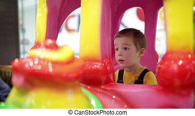 Boy in amusement train - Little boy swinging in colorful...