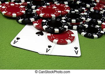 Two black aces over poker chips