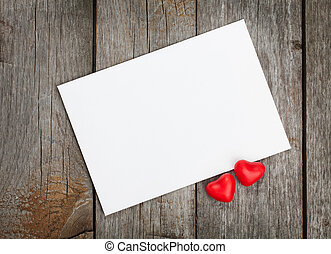 Valentines day blank gift card and red candy hearts on...