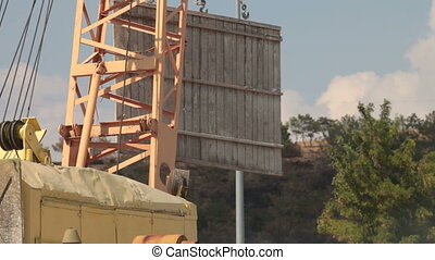 Crane lifts a wooden panel at construction site