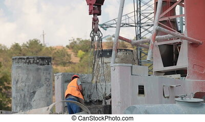 Worker at construction site by crane