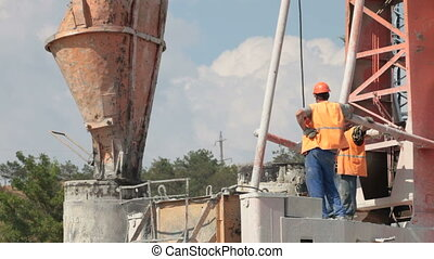 Builders poured concrete in bored piling machine at the...