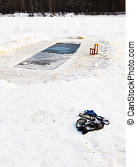 slippers and chair near ice hole in frozen lake in cold...