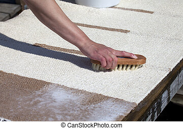 Scrubbing carpet on the dock