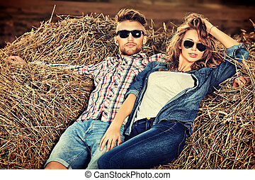 haystack - Romantic young couple in casual clothes sitting...