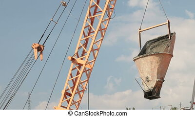 Crane lifts bucket of concrete at construction site