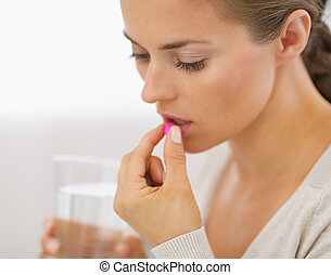Young woman eating pill