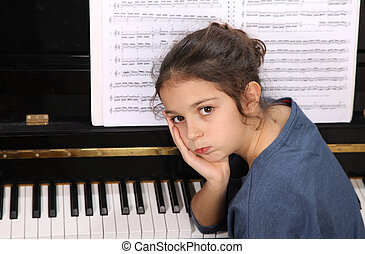 Piano lessons - Young girl sitting at a piano keyboard