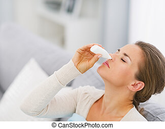 Young woman using nose drops