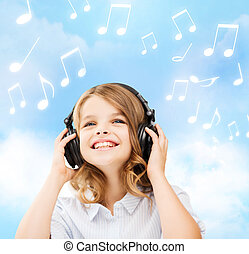 smiling little girl with headphones at home - home, leisure,...