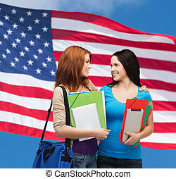 two smiling students with bag and folders - education and...