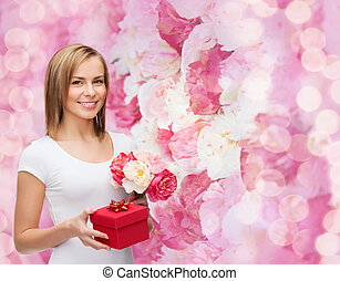smiling woman with bouquet of flowers and gift box -...