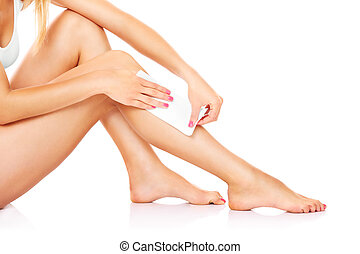 Waxing - A picture of a young woman waxing her legs over...