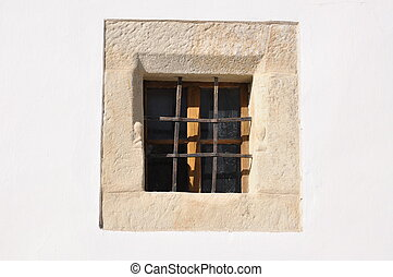 A small window on the facade of the old building