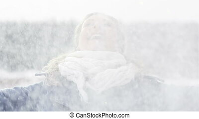 Snowfall - Slow-motion of a carefree young woman enjoying a...