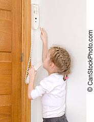 Little girl talking on the intercom at home