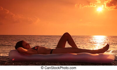 Relaxed young girl lying on the beach at sunset