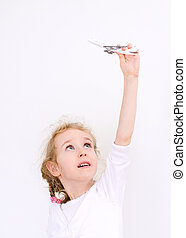 Little girl playing with model airplane.