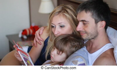 Happy family reading a book in bed