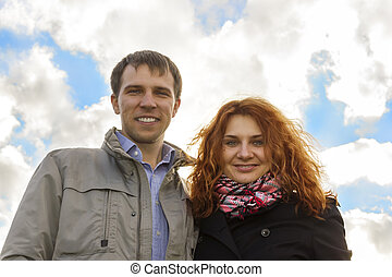 Outdoor happy couple in love against sky background